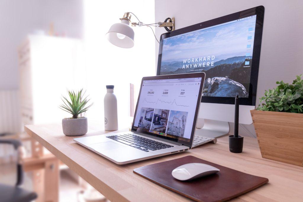 Deux ordinateurs sur un bureau, représentant l'environnement pour la création de site Web.