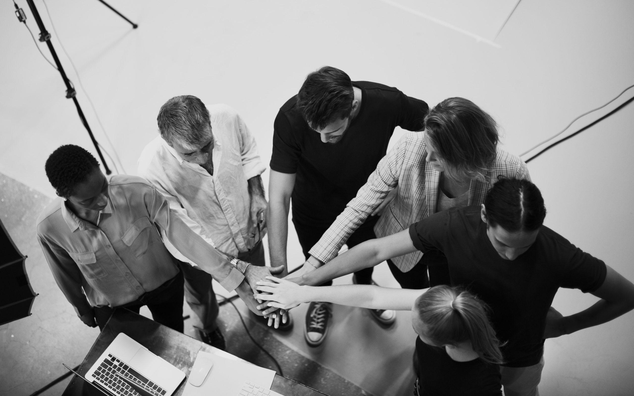 Image représentant un groupe de gens les mains les unes sur les autres en signe de solidarité: notre principale valeur.
