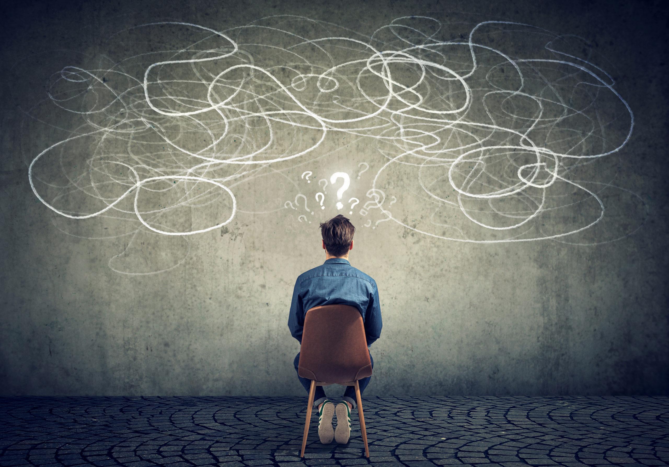 Homme d'affaire assis, confus face à un gribouillage sur un mur. Cela représente ses défis au quotidien.