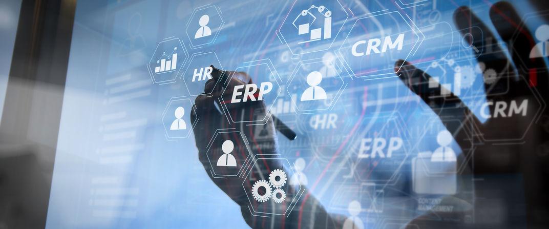 Une main écrit sur un écran transparent les secteurs gérés par un ERP-CRM.