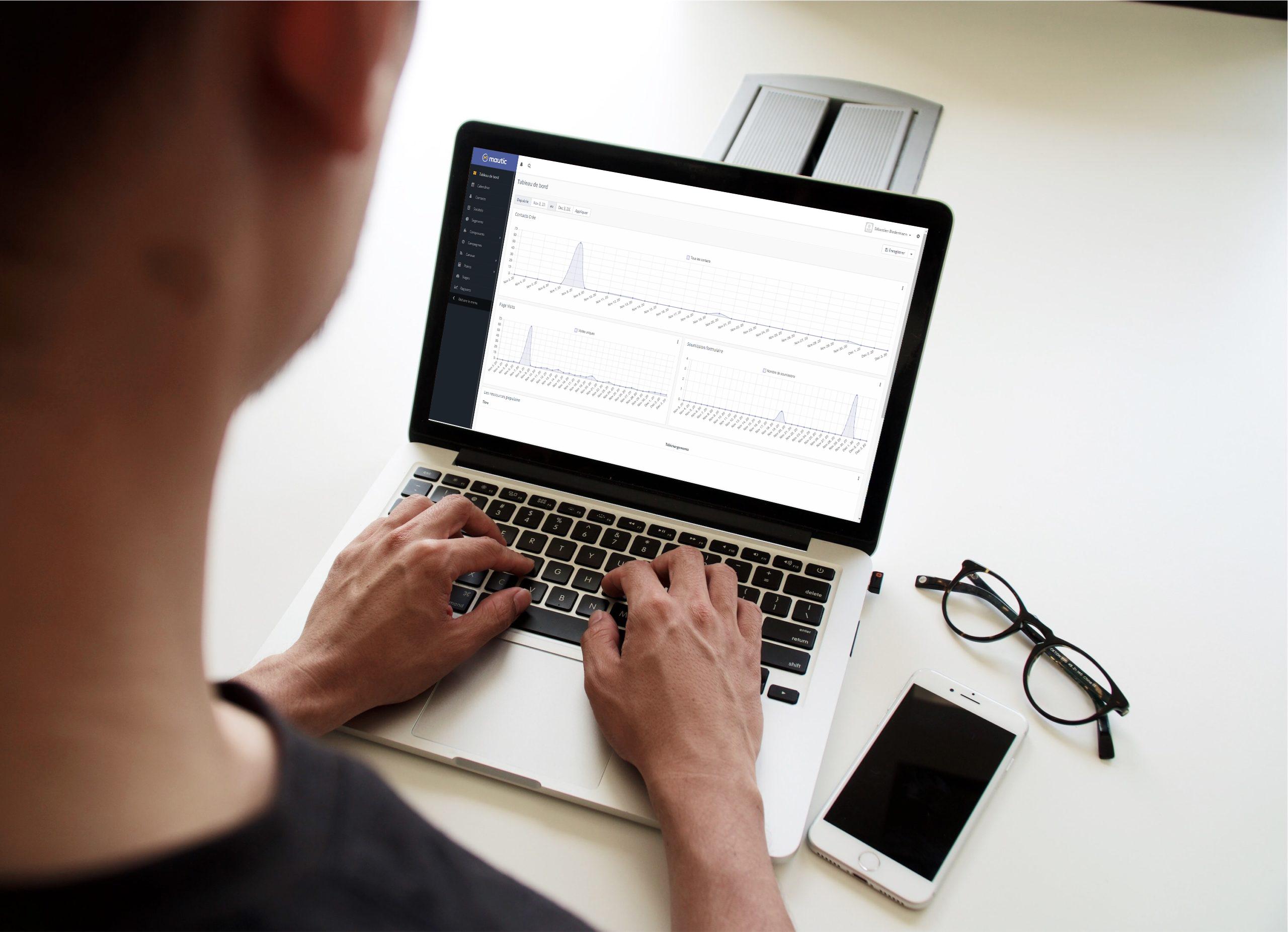 Personne travaillant sur un ordinateur portable. Sur l'écran on voit une fenêtre du logiciel de marketing automation Mautic.