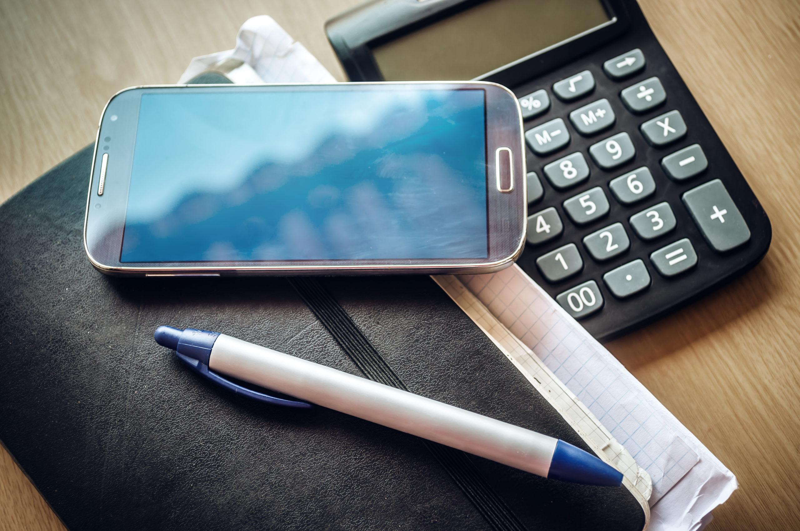 Un agenda papier, une calculatrice un stylo et un téléphone pour symboliser le télésecrétariat